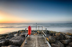 Sandbanks Jetty. A small jetty on the beach at Sandbanks in Poole, Dorset looking out towards Old Harry Rocks Royalty Free Stock Photo