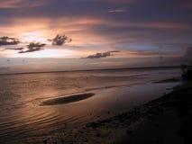 Sandbar Sunset. A pale sunset over a sandbar and beach. A heron hunts in the distance stock photos