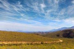Sandbergväg med fördunklad blå himmel Arkivbild