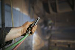 Sandblaster ελεγκτών ασφάλειας εκμετάλλευσης χεριών εργατών οικοδομών πρόσβασης σχοινιών οι λειτουργούσες deadman λαβές μεταστρέφ στοκ φωτογραφία
