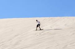 Sandboarding i den Atacama öknen Royaltyfri Bild