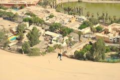 Sandboarding zur Stadt Stockfoto