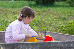 In the sandbox. Cute, little girl playing in the sandbox Stock Photography