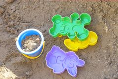 Sandbox with close-up. Sandbox with children`s toys, colorful plastic buckets, molds, saucers. Summer, a game in the sand Royalty Free Stock Image