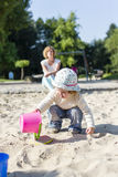 In the sandbox. Mother and toddler out together on the playground. The mother is sitting in the edge in the blur and oversees her little daughter Royalty Free Stock Images