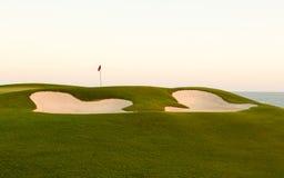 Sandbunker framme av den golfgräsplan och flaggan Royaltyfria Bilder