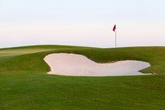 Sandbunker framme av den golfgräsplan och flaggan Arkivbilder