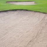 Sandbunker und grünes Gras Stockfotos