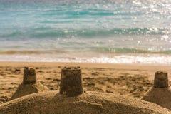 Sandburg auf einem Strand im Sonnenschein mit Meer im Hintergrund und im offenen Raum stockfotografie