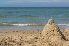 Sandburg auf Strand mit Ozean im Hintergrund Stockfotos