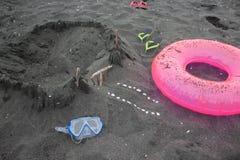 Sandburg, Sandalen, schwimmende Gläser Sommer und Reisekonzept Strandleben Reise oder Seeferienkonzept Stockfotografie