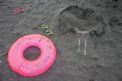 Sandburg, Sandalen, schwimmende Gläser und sich hin- und herbewegender Ring Sommer und Reisekonzept Reise oder Seeferienkonzept Lizenzfreies Stockbild