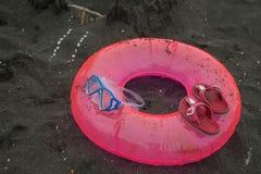 Sandburg, schwimmende Gläser, rosa Sandalen Reise oder Seeferienkonzept Strandleben In den Sommerferien Stockfotografie