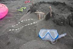 Sandburg, schwimmende Gläser, rosa Sandalen Sommer und Reisekonzept Stockfotografie