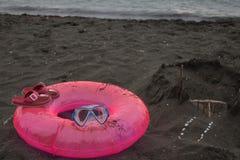Sandburg, schwimmende Gläser, rosa Sandalen Sommer und Reisekonzept Strandleben In den Sommerferien Lizenzfreie Stockfotos