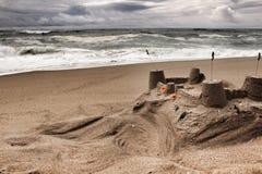 Sandburg, tapferer Ozean, Felsformationen und bewölkter Dramahimmel auf dem Strand Lizenzfreies Stockfoto