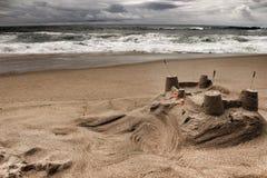 Sandburg, tapferer Ozean, Felsformationen und bewölkter Dramahimmel auf dem Strand Stockbild