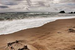 Sandburg, tapferer Ozean, Felsformationen und bewölkter Dramahimmel auf dem Strand Stockbilder