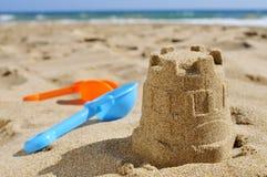 Sandburg und Spielzeug schaufelt auf dem Sand eines Strandes Lizenzfreies Stockbild