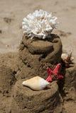 Sandcastle με τον αστερία, το κοράλλι και το θαλασσινό κοχύλι στην αμμώδη παραλία Στοκ Φωτογραφία