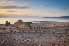 Sandcastle на пляже на восходе солнца Стоковое Изображение