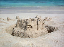 Sandcastle. A sandcastle stands at the water's edge on a Hawaiian beach as gentle waves lap the shore Royalty Free Stock Photos