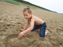 Sandcastle at the beach. Boy making a sand castle at the beach Stock Photography