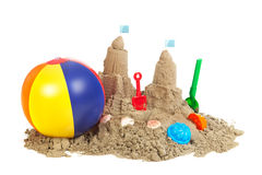 Sandcastle at the beach. With platic toys isolated over white background Royalty Free Stock Photo