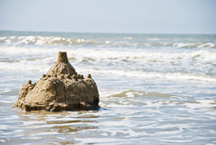 Sandcastle on the beach. Sandcastle destroyed by the high tide Stock Image