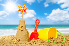 Sandcastle On The Beach. Sandcastle with bucket and spade with beach blur background Royalty Free Stock Images