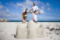 Sandcastle on beach, focus on two generation family in background, portrait, surface level Royalty Free Stock Image