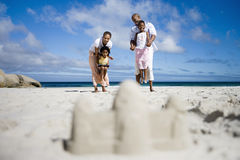Sandcastle on beach, focus on two generation family in background, portrait, surface level Stock Photography