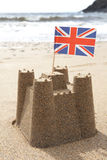 Sandcastle On Beach With Union Jack Flag. Flying stock image