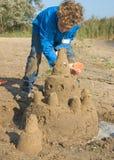 Sandcastle della costruzione del ragazzo Fotografie Stock
