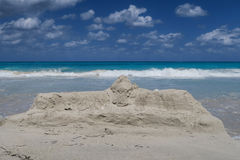 Sandcastle dissolved. A beautiful hot summer day in Cuba, sandcastle is being washed away by the waves of the Atlantic Ocean Royalty Free Stock Image