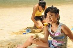 sandcastle för strandbyggnadsflickor Royaltyfri Foto