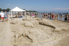 Sandcastle Festival - Cobourg, Ontario July 2011. Visitors to Cobourg Beach cool off in the water and admire sculptures built of sand on the shores of Lake Royalty Free Stock Photos