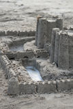 Sandcastle with Moat. Castle made of sand with water in the moat Stock Image