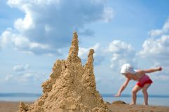 Sandcastle and playing child Royalty Free Stock Photos