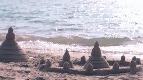 Sandcastle przeciw oceanowi pluskocze wodę odbija światło słoneczne zbiory wideo