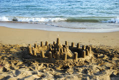 Sandcastle and the Sea. A small sandcastle with a white flag on beach with waves on the background Royalty Free Stock Image