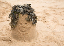 Sandcastle with seaweed making a happy face Royalty Free Stock Photo