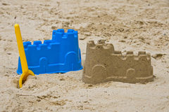 Sandcastle with shovel. Sandcastle with a yellow shovel Stock Photos