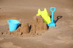 Sandcastle and snd pie building with bucket and spade. Beach with sandcastle, buckets, spade and sand pie on beach. Creative sand formation. An activity enjoyed Stock Photo