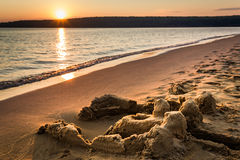 Sandcastle Sunset. A golden sunset bathes the eroded remnants of a sandcastle on a sandy beach Royalty Free Stock Photography