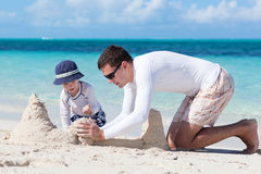 Sandcastle time!. Little kid and his father building sandcastle Stock Photography