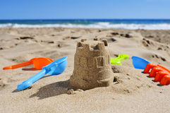Sandcastle and toy shovels on the sand of a beach Stock Image