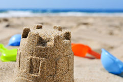 Sandcastle and toy shovels on the sand of a beach Royalty Free Stock Photo