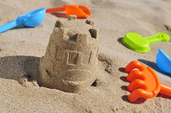 Sandcastle and toy shovels on the sand of a beach Royalty Free Stock Images