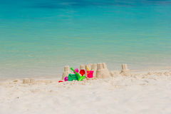 Sandcastle at white beach with plastic kids toys Royalty Free Stock Image